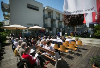 Der Gottesdienst fand bei schönstem Wetter vor dem Haus Erna in Wien statt / Le culte a eu lieu par un très beau temps devant la Haus Erna, à Vienne