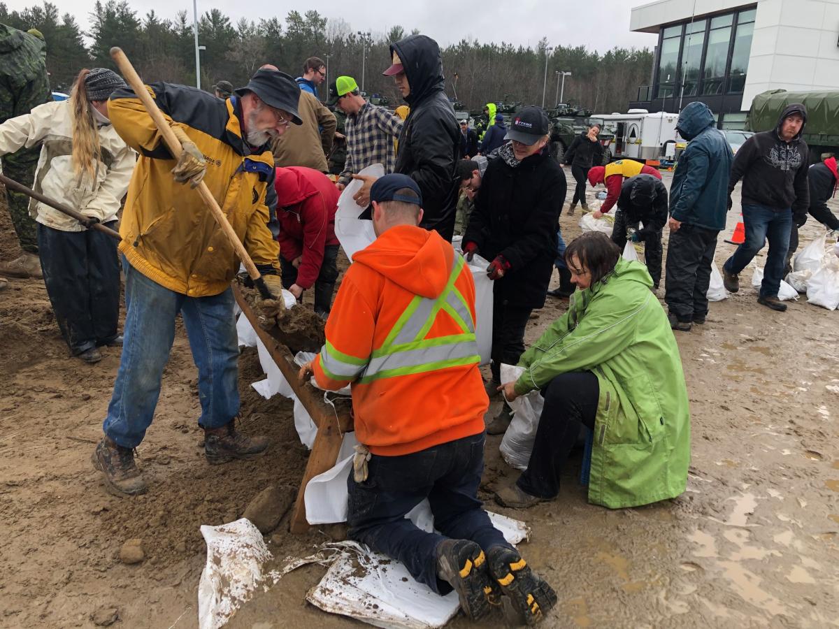 Les bénévoles remplissent des sacs de sable à Constance Bay. / Freiwillige füllen Sandsäcke in Constance Bay.